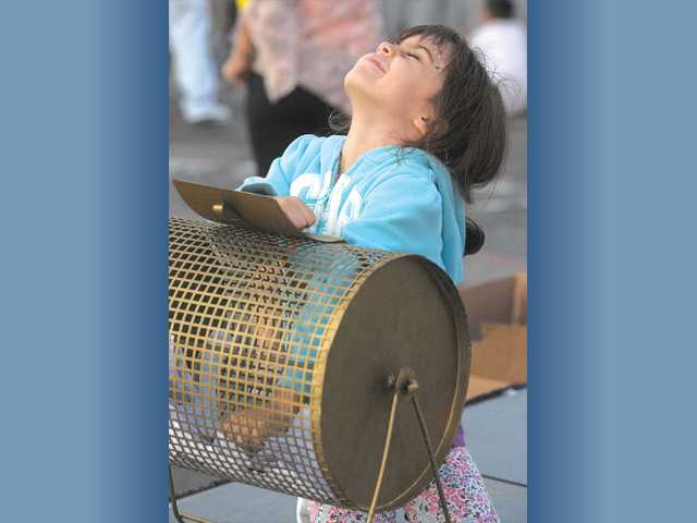 Sofia Donapetry, 4, closes her eyes as she picks raffle tickets from the drum at the Fourth Annual Stay Green Inc. Empoyee Appreciation Carnival.