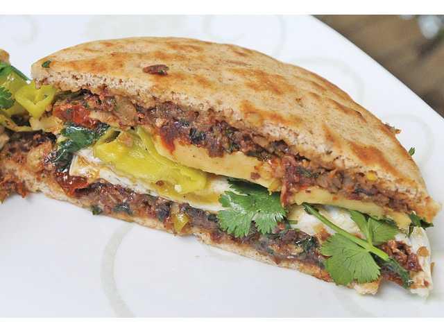 A Gouda fried egg sandwich with walnut raisin pesto, a vibrant alternative to boring breakfast sandwiches.