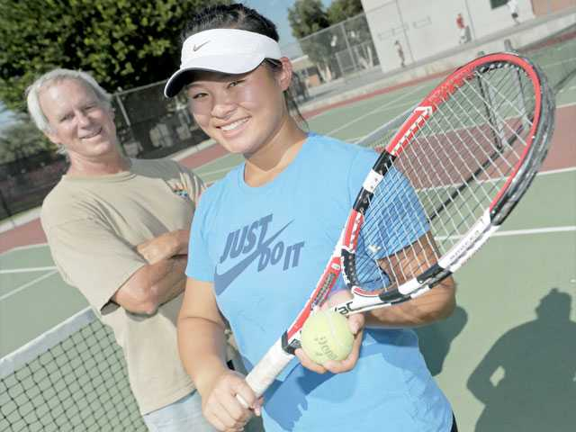 Hart High head tennis coach Chris Mansfield, left, has coached three of Indians sophomore Lauren Dam's uncles. Dam is in her second varsity season.