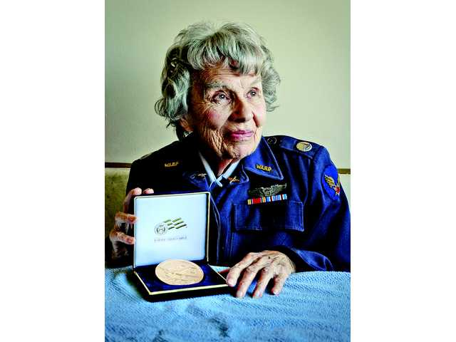 Mary Lou Neale poses with a bronze replica of the Congressional Gold Medal she received in Washington, D.C., last year. Each of the wartime Women Air Force Service Pilots received one.