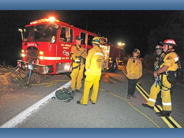 Los Angeles County firefighters wait for coroner's officials on Lake Hughes Road, where two vehicles were found off the side and about 200 feet down in the canyon below in the Angeles National Forest, north of Castaic on Thursday.