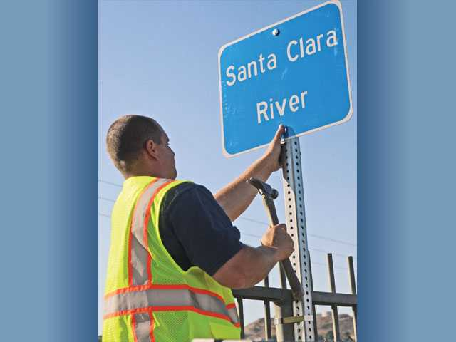 Santa Clarita street-maintenance worker Mike Doroginsky mounts a sign to a pole on the Sand Canyon Road overpass above the Santa Clara River in Santa Clarita on Thursday.