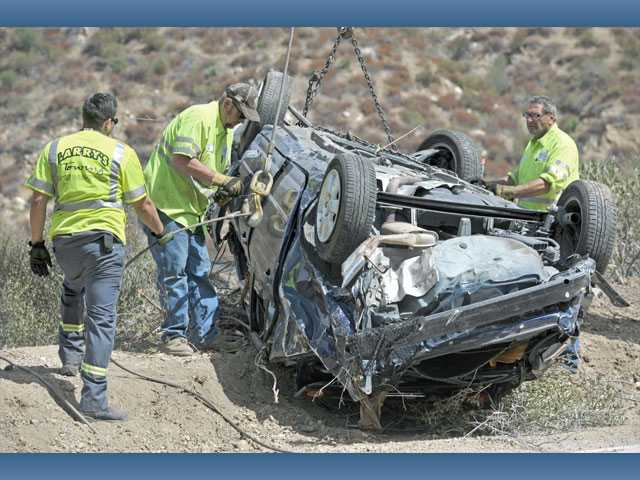 Tow truck operators work with a Toyota Corolla after being lifted about 200 feet by a crane on to Lake Hughes Road, north of Castaic,