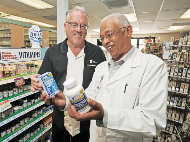Mike Quick, left, national vice president of Good Neighbor Pharmacy Development and pharmacist Tony Olivier hold products at Valencia Pharmacy in Newhall.