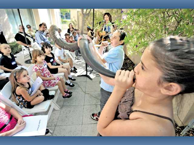 Wendy Hersh, left leads the children's sing along as Daniel Bratslavsky, 10, and Dina Blazer, right, blow the shofar, a ram's horn, for Rosh Hashana.