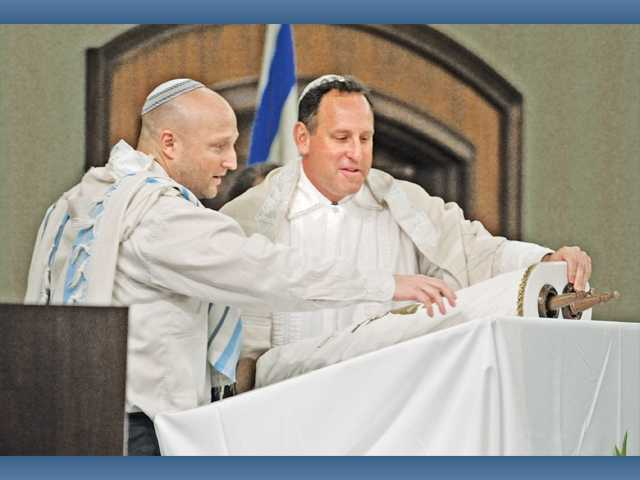 Temple Beth Ami member Rob Herschenson, left, and Rabbi Mark Blazer lay the Torah on the altar for Rosh Hashana held at the Hyatt Regency Valencia in Valencia on Thursday morning.
