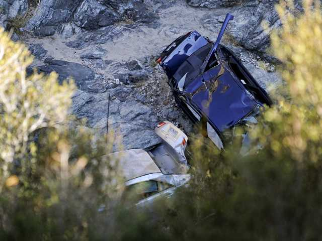 Two cars at the bottom of a remote mountain are recovered in Castaic, Friday.