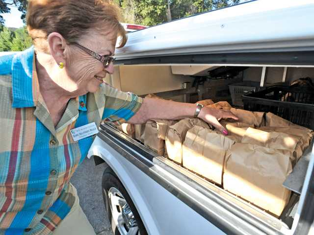 SCV Senior Center volunteer home food delivery driver Jackie Cortes counts the spaghetti meals in her truck at the SCV Senior Center that are ready for home delivery to seniors on Thursday.