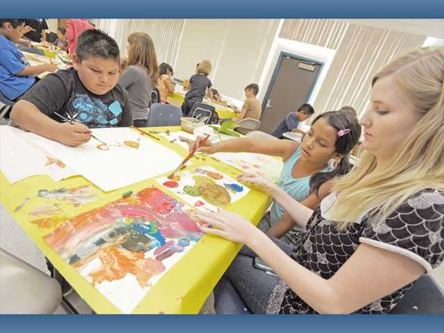 From left, third-graders Kevin Salgado and Yulieth Lopez, both 8, paint with the help of California Institute of the Arts student Sarah Heysel at Newhall Elementary School on Monday.