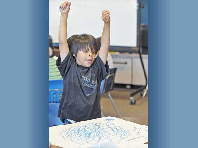 Third-grader Jareth Ventura, 8, cheers as he finishes a drawing.