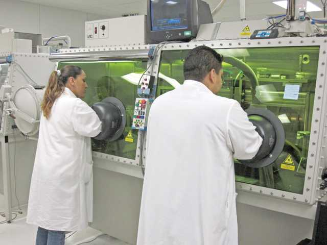 Quallion LLC lab employees work in the dry room to avoid contamination recently. The green-lit containment chamber, which is filled with a nitrogen/argon atmosphere, reduces exposure to contaminants from unfinished products.