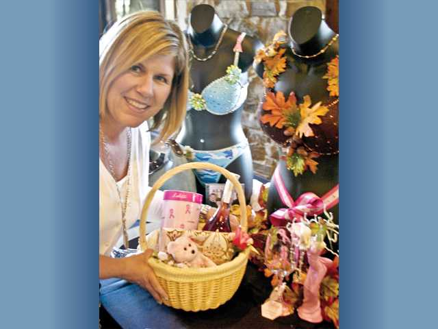 "Santa Clarita Councilwoman Laurie Ender with her basket of goodies and the ""Tie a Pink Ribbon Round the Old Oak Tree"" bra donated by Sandi Naba."