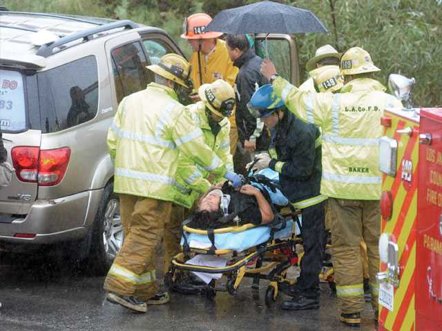 Firefighters hold an umbrella over a woman as she is loaded onto a gurney after she lost control of her SUV in heavy rain on northbound Interstate 5, went down an embankment and through a fence ending up on Castaic Road near Tapia Canyon Road in Castaic on Wednesday morning.