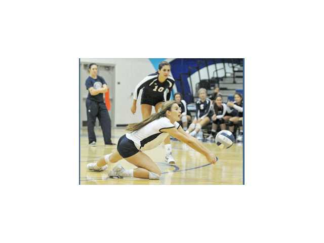 Saugus libero Kristin McCord goes for a dig as outside hitter Jaclyn Clark looks on Wednesday at Saugus High.
