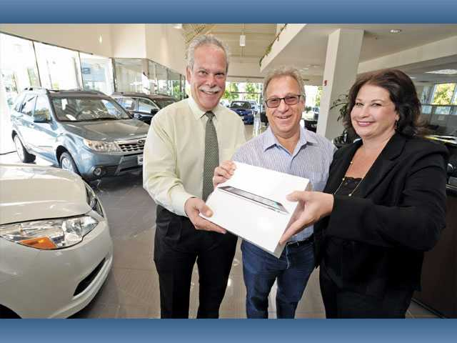 Galpin of Santa Clarita General Manager Joe Ferezy, left, and Galpin of Santa Clarita Community Relations Debi Acker-Zolnoski, right, present an Apple iPad to Evan Mendelzon at Galpin Subaru on Thursday.  Mendelzon won the dealership's drawing at the SCV Community Expo in September.