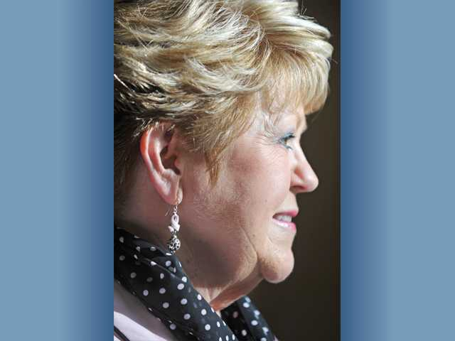 Barbara Larson sports pink ribbon earrings in honor of breast cancer awareness.