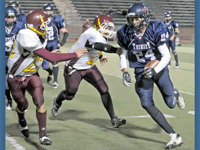 Trinity's James Brooks, right, tries to evade Maricopa defenders Brandon Kingsbury, left, and Kris Houston during Friday night's game at College of the Canyons. Brooks caught three passes for 95 yards and had three touchdowns in the game.