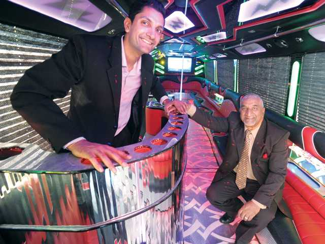 Lightning Limo Vice President Vin Bali, left, and his father and company president, Kuldip Bali, with their new 50-person party bus.