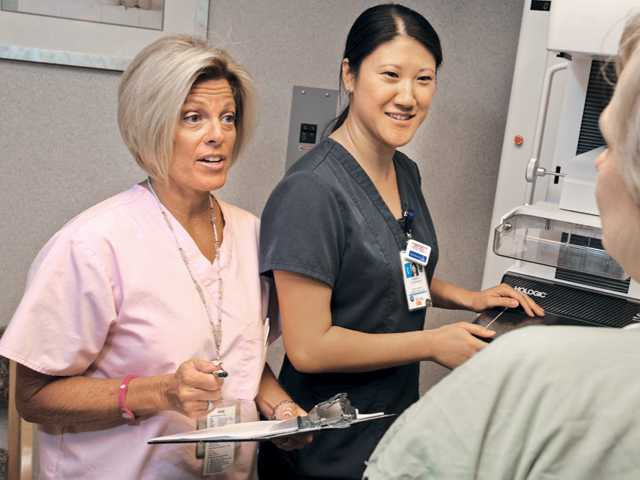 Breast Health Navigator Mindy Burgess, RN, left, and Sandy Cunanan, breast imaging mamo tech lead, center,  prepare a patient for breast imaging at Henry Mayo Newhall Memorial Hospital Sheila R. Veloz Breast Imaging Center on Thursday.