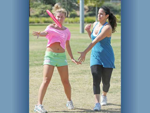 Catherine Herrick, 20, left, tosses a throwing disc as Chantal Khalilieh, 19, defends in a game of ultimate on Monday at Valencia Heritage Park. For another photo, see Local, A9.