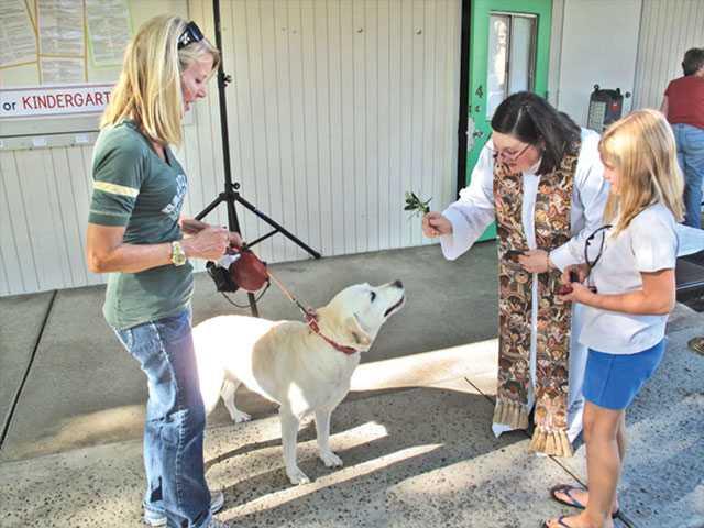 The Rev. Susan Bek, left, blesses a pet during a celebration of a blessing of the animals, a tradition that has roots that date back to the 13th century, at St. Stephen's in Newhall on Sunday.
