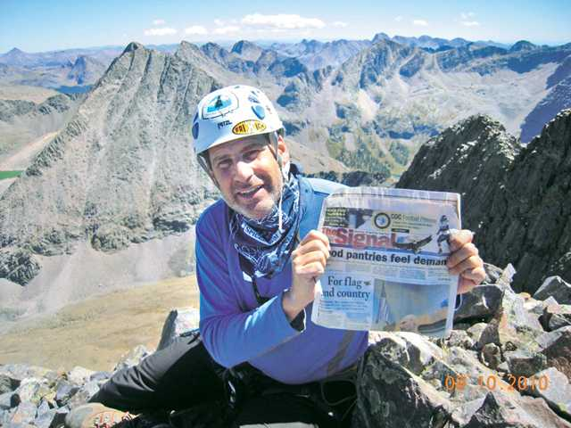 Andrew Pfeffer, of Saugus, holds a copy of The Signal on the summit of Vestal Peak in the Grenadier Range of the San Juan Mountains in Colorado.