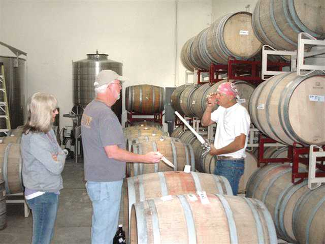 On bottling day at Cantara Cellars, the Brileys watch fellow wine-maker Marlow Barger taste their Nuggucciet Cellars Pinot Noir prior to bottling. Barger also produces his label, called Plan B, at the Camarillo facility.