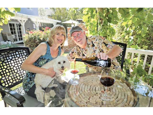 Nancy and Russ Briley, joined by their dog Gucci, enjoy a bottle of their wine under their backyard grape arbor at their home in Castaic on Sept. 24.