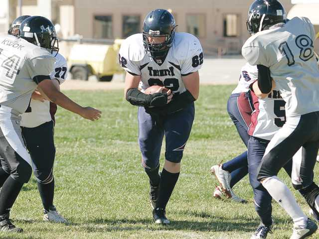 Trinity offensive lineman/fullback Cameron Taylor, center, looks for room to run against Antelope Valley Christian on Saturday at Antelope Valley Christian School. Trinity won 60-8.