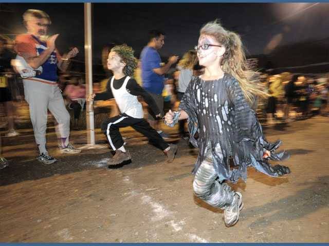 Mavrik Farris, 7, left, and Lena Strahann, 7, dressed as zombies, cross the finish line in the Kids K race.