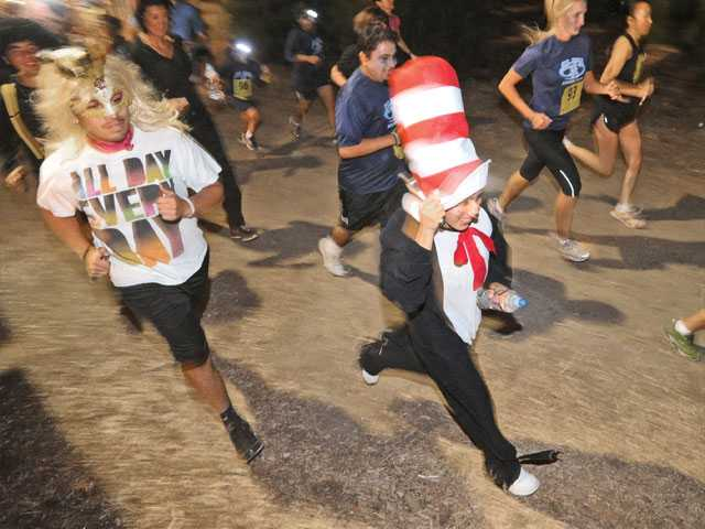 Kenia Osores, right, of Canyon Country, dressed as The Cat in the Hat runs in the third annual Monster Dash 5K at Nancy's Ranch in Valencia on Saturday.
