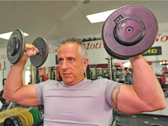 Madia demonstrates a dumbbell overhead press at Results Fitness.