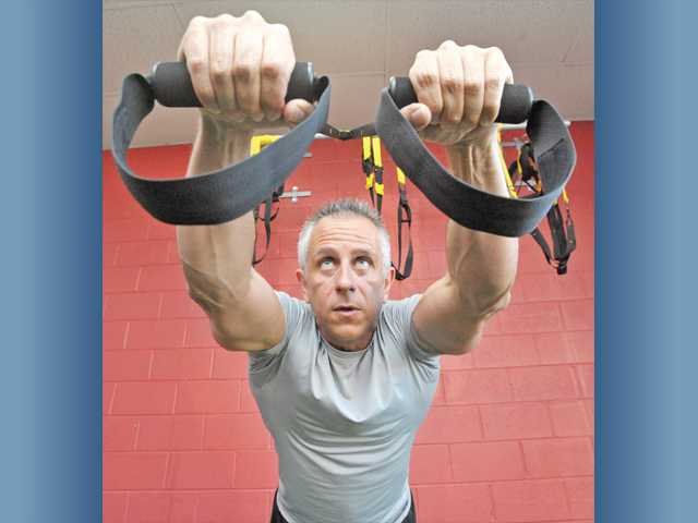 James Madia demonstrates dumbbell pushups with a TRX suspension trainer.