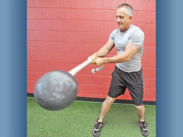Madia demonstrates a tornado ball exercise. In his first 23 weeks, Madia dropped 9 percentage points of body fat by just doing metabolic classes.