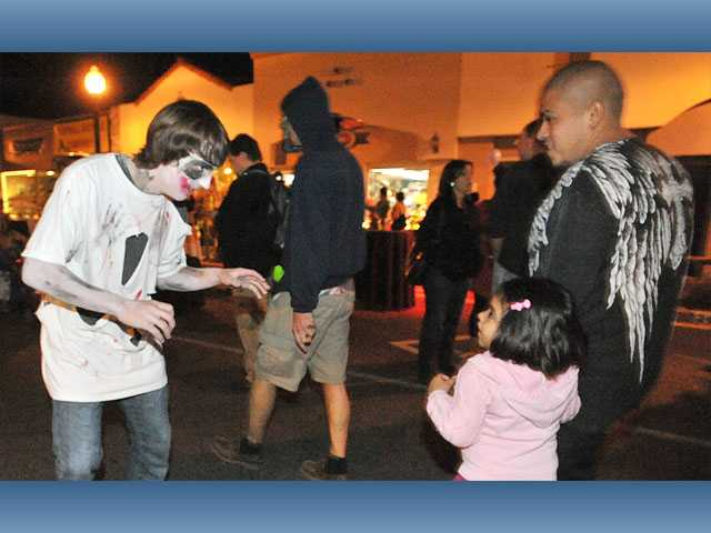 Andrew Mangers, 16, left, spooks Brianna Angel, 4, and her father, Chris Angel, of Newhall, as zombies roam down Main Street for the Senses block party in Newhall on Thursday.