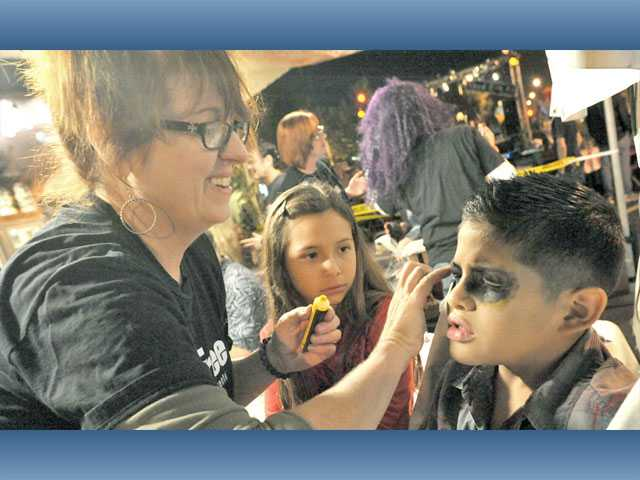 Paula Dwyer of The ARTree Community Arts Center, left, paints black eyes on Alex Solis, 8, right, as friend Monse Soto watches during the Senses block party.