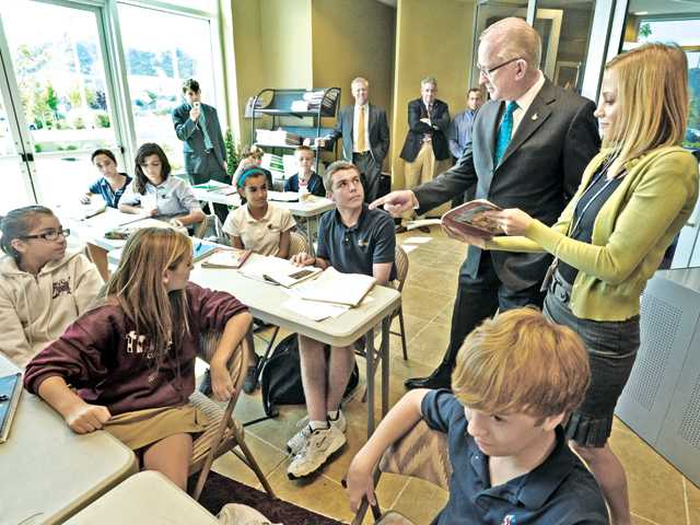 "Congressman Howard ""Buck"" McKeon, second right, chats with seventh grade Latin teacher Jenny Llamas, right, and her class at Trinity Classical Academy in Santa Clarita on Thursday."