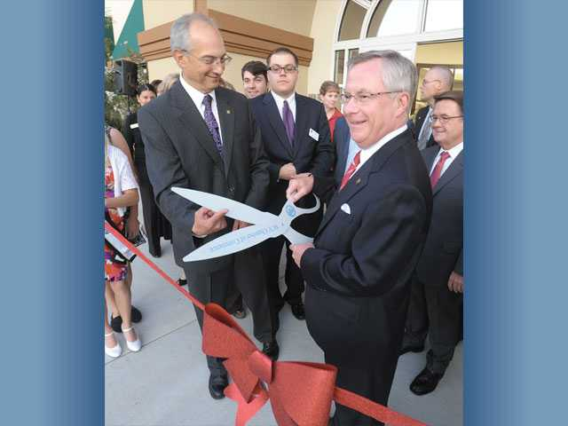 Bank of Santa Clarita Chairman of the Board Frank Di Tomaso, left, and Hicken get ready to cut the ribbon.