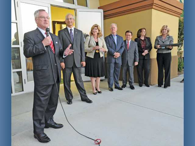 James Hicken, left,  President and CEO of Bank of Santa Clarita welcomes guests at the grand opening of the location in Valencia on Thursday.