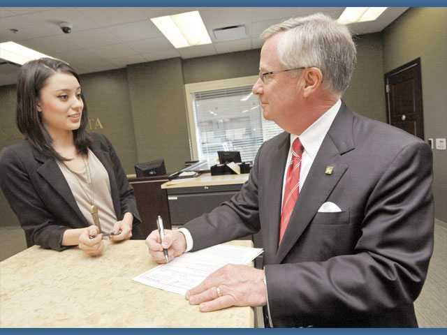 Client services representative Nicole Lopez, left, and Hicken look over paperwork at the Bank of Santa Clarita in Valencia.