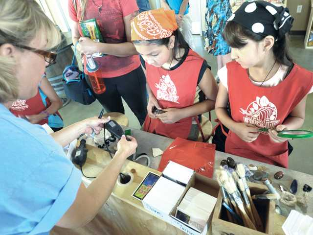 Sisters Haley, 9, and Kaelyn Ortega, 7, right, get instruction on rock-cleaning tools from education coordinator Debbie Hattox, left, at Dig It! The Fossil Workshop store at the Westfield Valencia Town Center Mall in Valencia on Thursday.