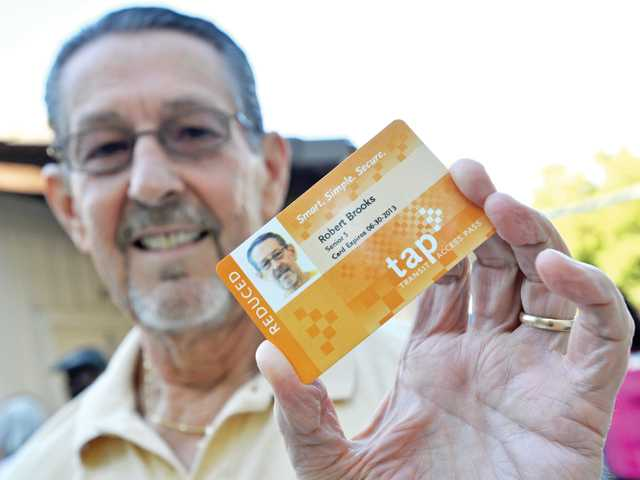 Senior transit ambassador Robert Brooks shows his Transit Access Pass card at the Santa Clarita Valley Senior Center in Newhall. All transit users will be required to use the TAP card starting on Nov. 1.