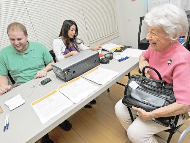 Jeanne Mares, 87, right, shares a laugh with Patrick Bryant, left, and Grace Estrada of Santa Clarita Transit as they process her TAP card application at the SCV Senior Center.