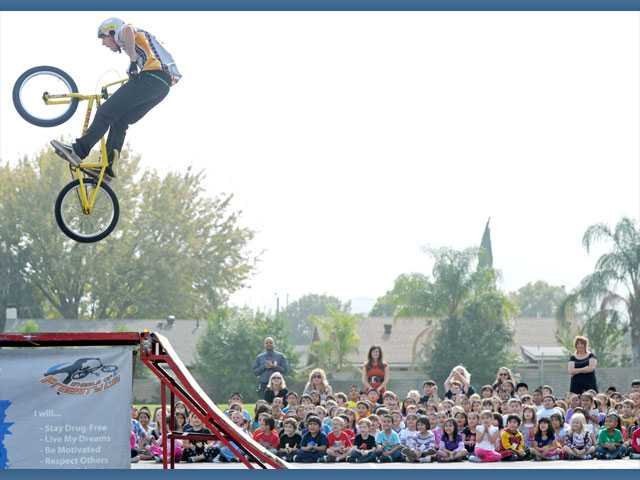 Kindergartners through third graders watch as Sean Logan takes to the air on his BMX bike.