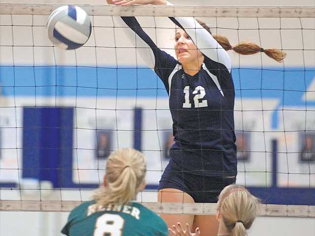 Saugus outside hitter Sarah Blomgren (12) taps the ball over the net as Canyon's Kaitlyn Reiner (8) and Courtney Spackman look on Tuesday at Saugus High School. The Centurions clinched a share of the Foothill League title.
