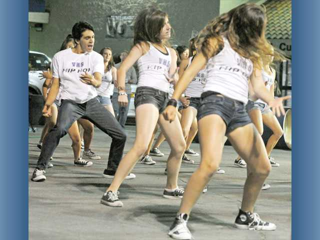 Valencia High senior Nicholas Villarreal, 17, left, performs with the school's hip-hop team during a pep rally at Power Ford Valencia on Wednesday. Chick-fil-A, the Santa Clarita Valley Food Pantry, Farmer John and the Ford dealership were on hand to support the Valencia Vikings and the Hart Indians ahead of their televised football matchup on Friday night.