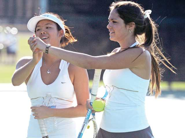 West Ranch doubles team Lena Poonnopatam, left, and Gabrielle Morici celebrate after winning a set against Hart on Wednesday at West Ranch High.