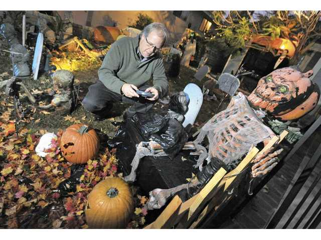 Rob Tezai sets up the music CD player for the talking pumpkins in the front yard at Rodeffer House in Saugus.