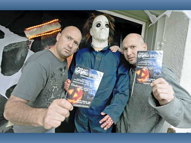 "Brothers William, left, and Kirk Landeen pose with a figure representing Michael Myers, the antagonist of the ""Halloween"" film series, and hold up fliers for their haunted house."