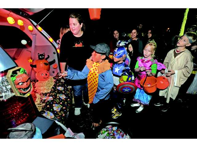 Linda Cavatail, of Valencia, directs costumed children who attended the Trunk-Or-Treat Fall Festival as they toss ping-pong balls painted as eye balls into jack-o'-lanterns in the Eye Ball Toss game set up in the back of her SUV at Valencia United Methodist Church in Valencia on Wednesday night.